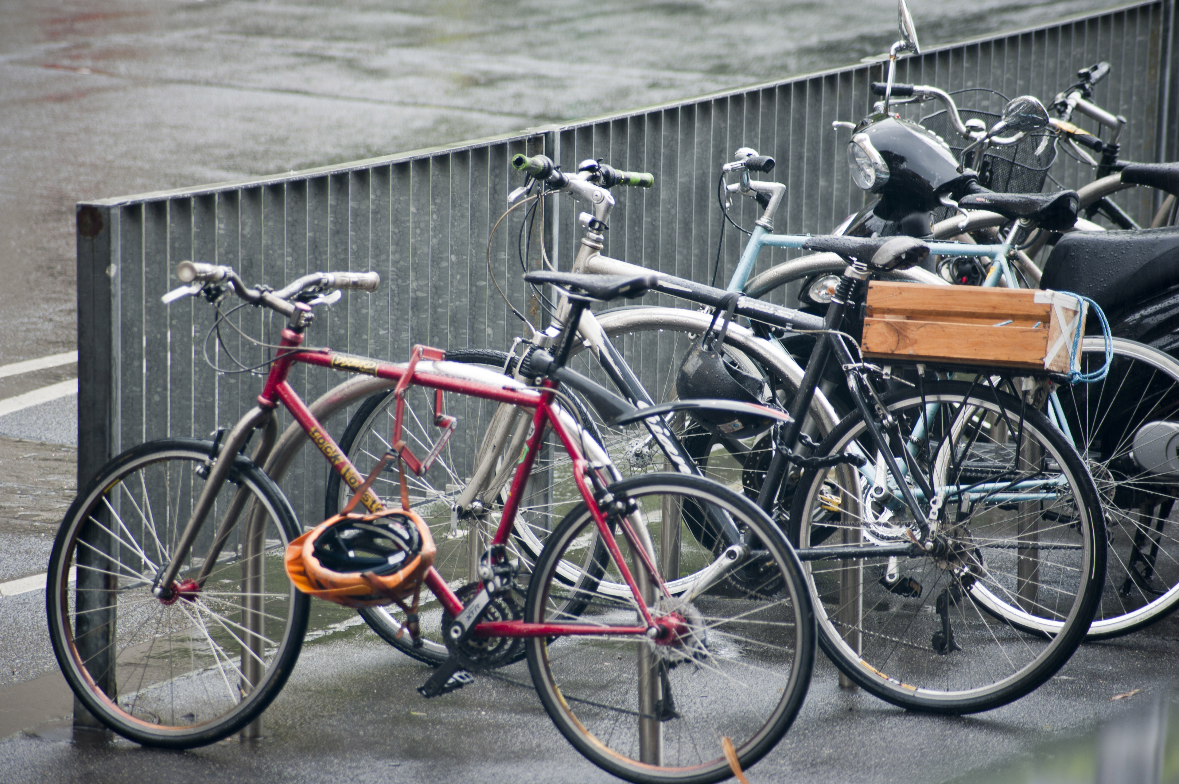 Various bicycles parked and chained at a city street bike rack.