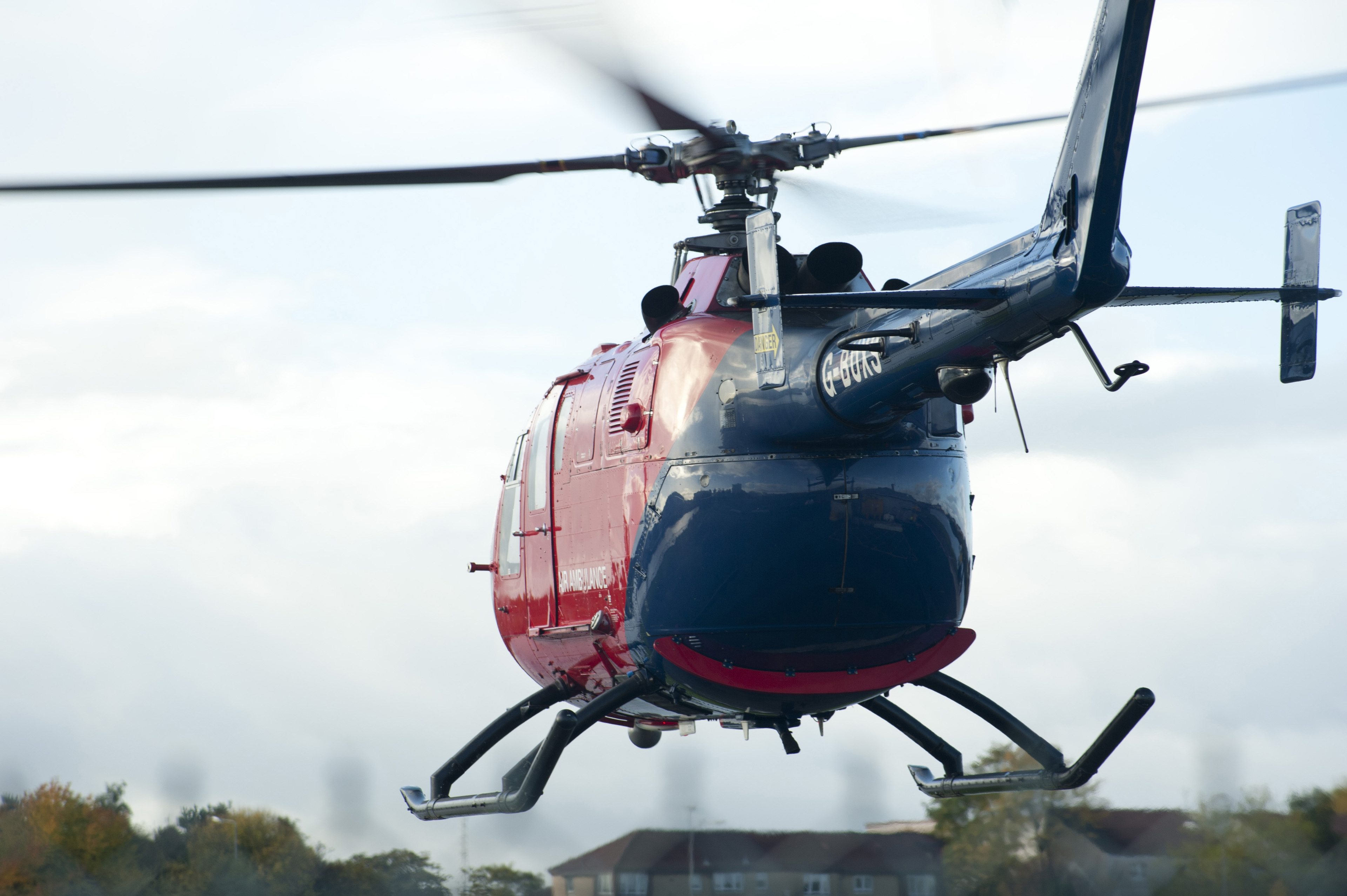 Red Helicopter Hovering with Blurred Rotating Blades as seen from Behind