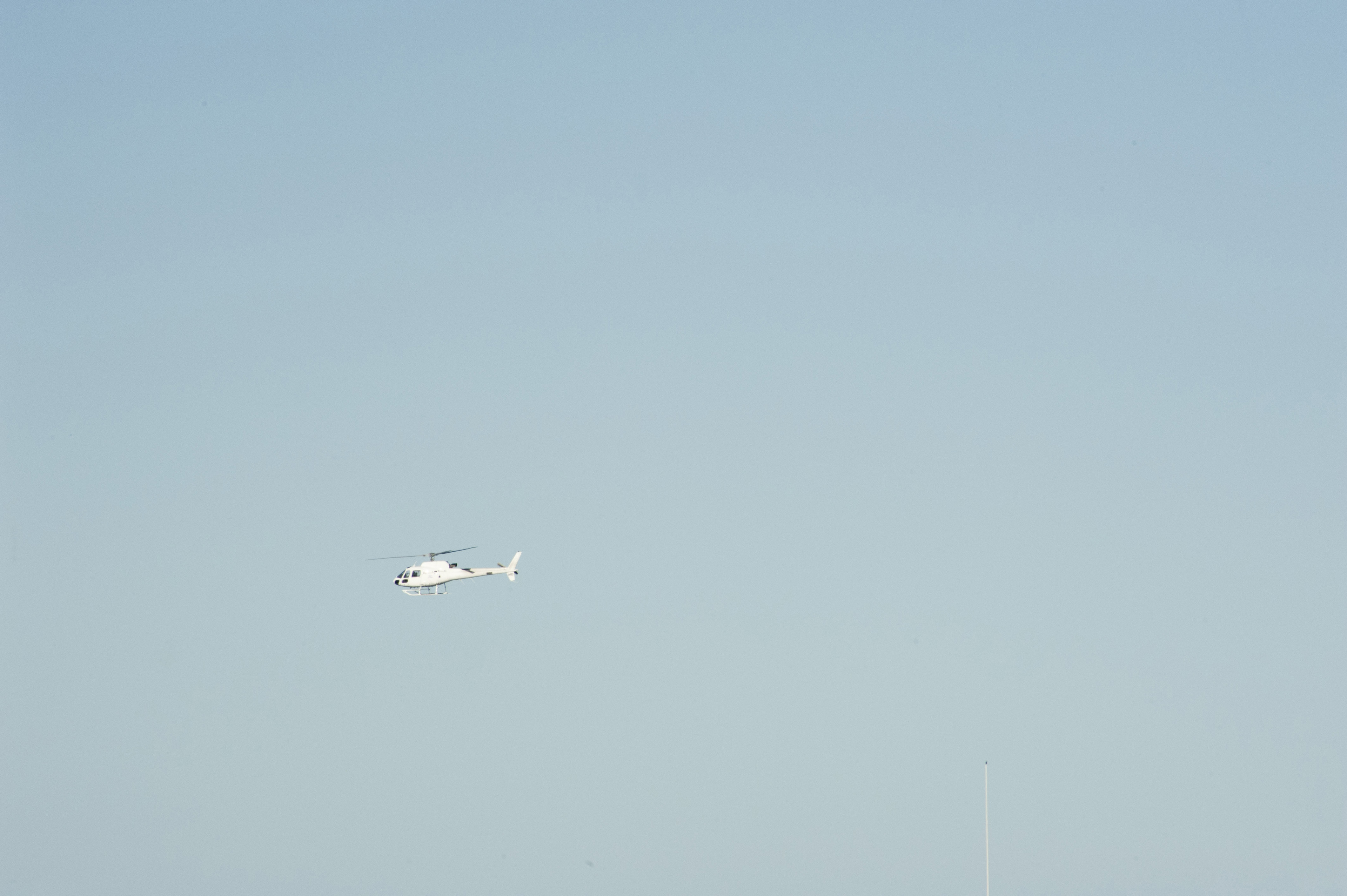 Side View of Helicopter Flying in Big Clear Blue Sky with Copyspace