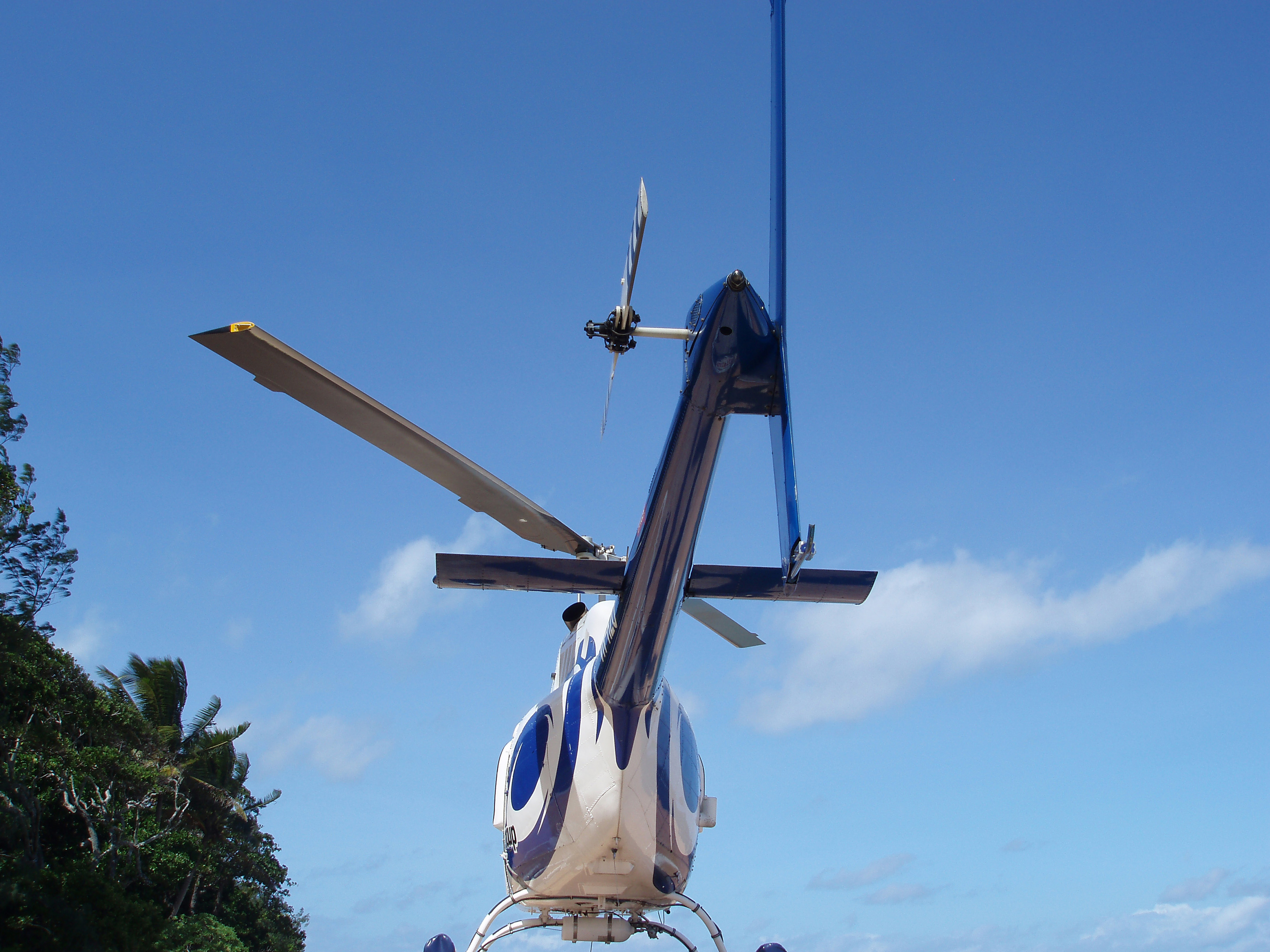 Rear low angle view of a parked helicopter showing the rotary blade on the tail and overhead rotor for lift against a clear blue sky