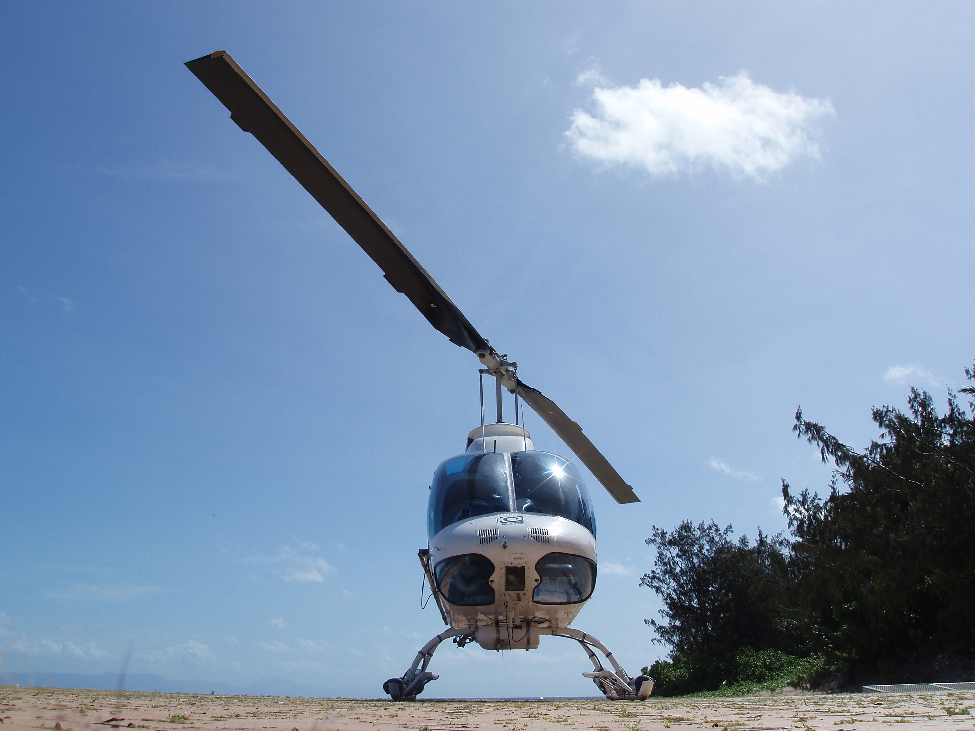 Low Angle View of Landed Helicopter on Ground with Sunny Blue Sky