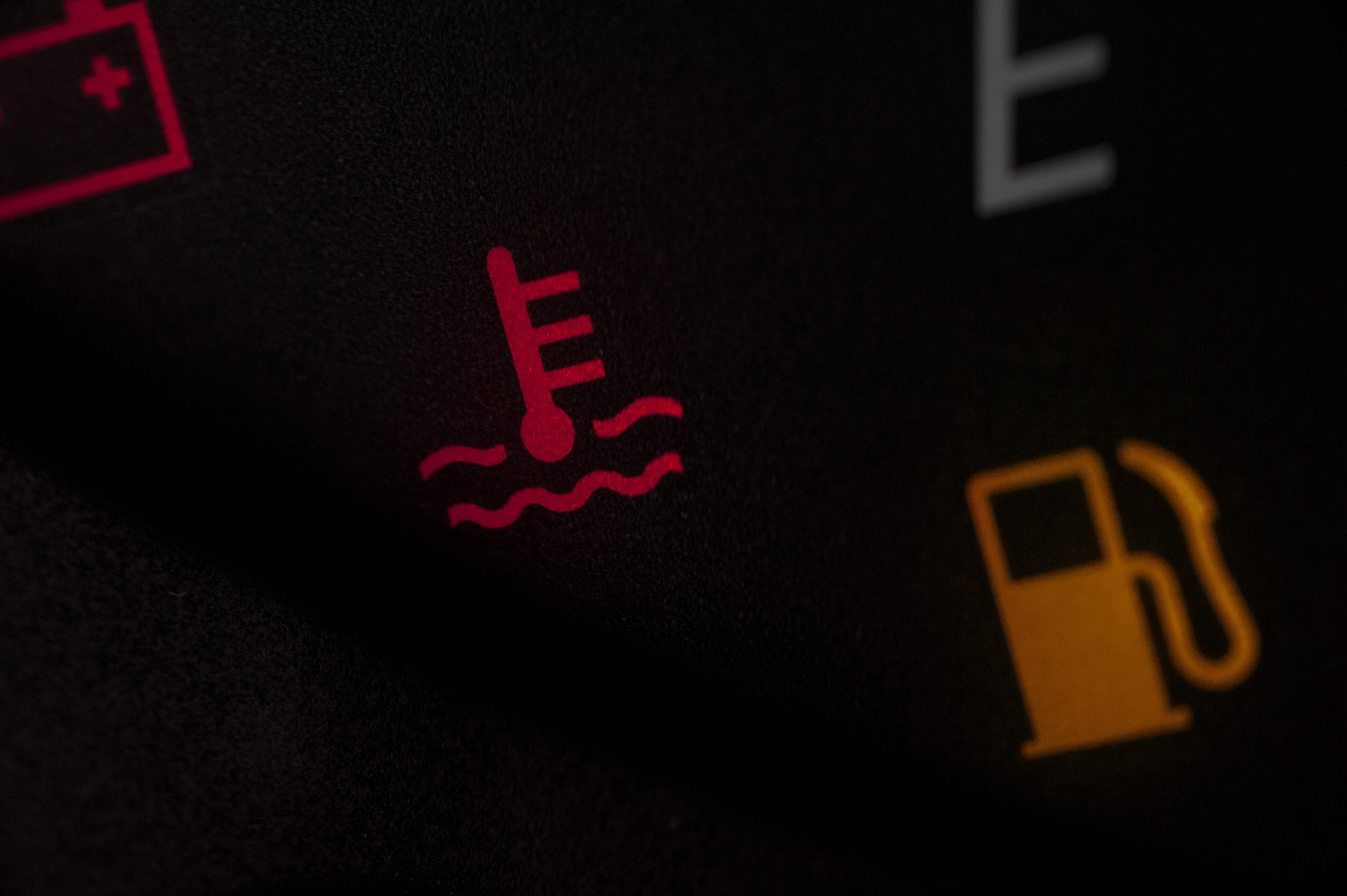 Low fuel warning light in a car illuminated on the dashboard together with a temperature waning