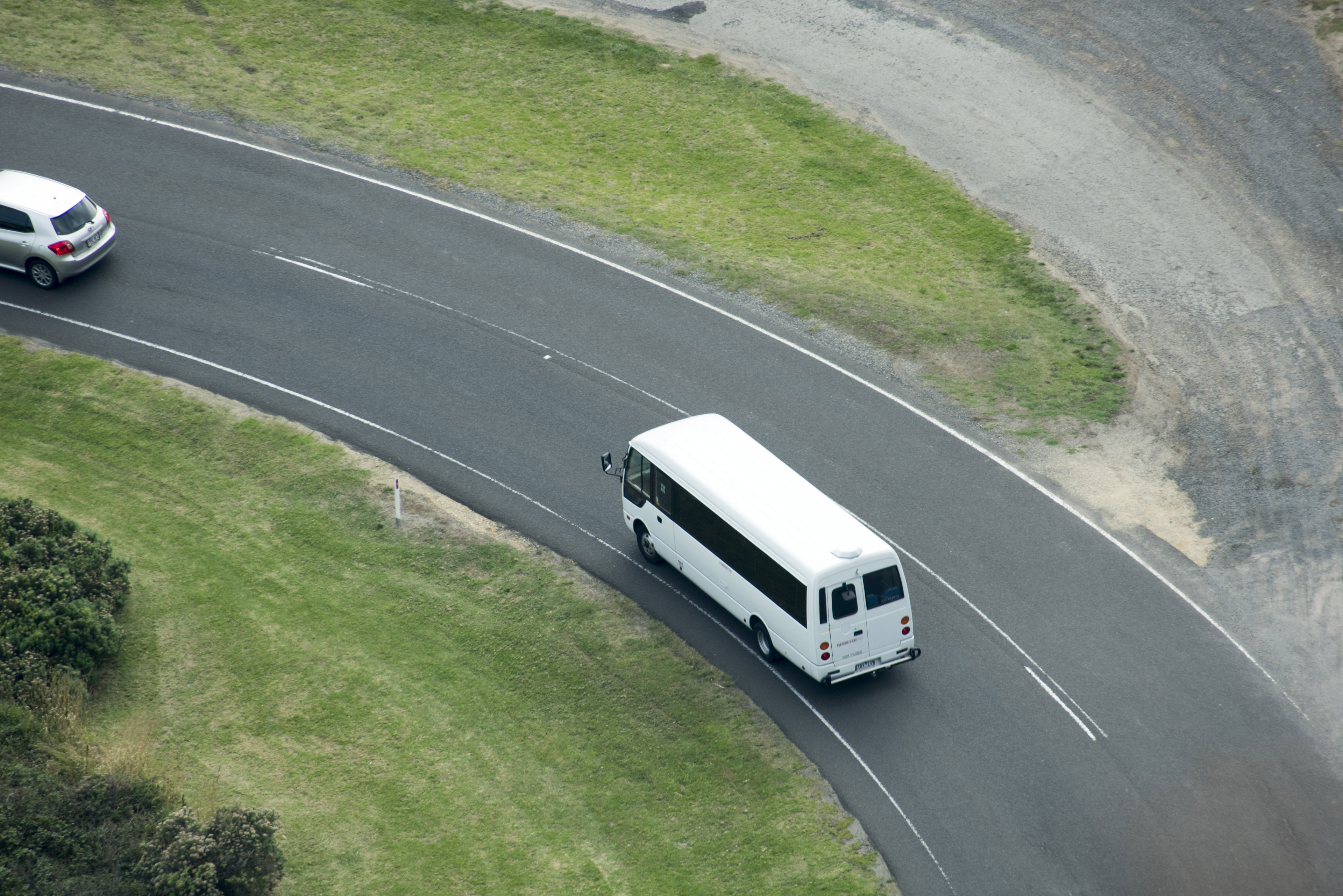Aerial view of mini bus going along winding asphalt road