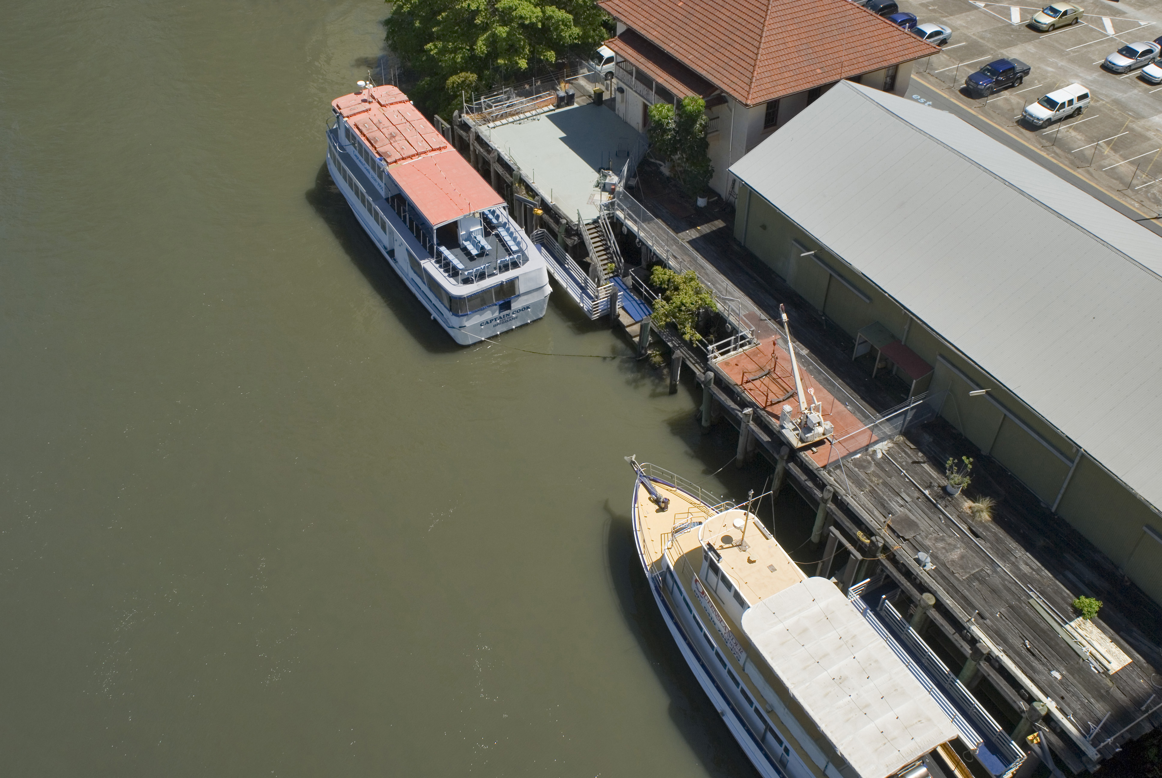 Overhead View of River Boats Docked at Ferry Terminal Buildings on Rivers Edge with Parking Lot in Background