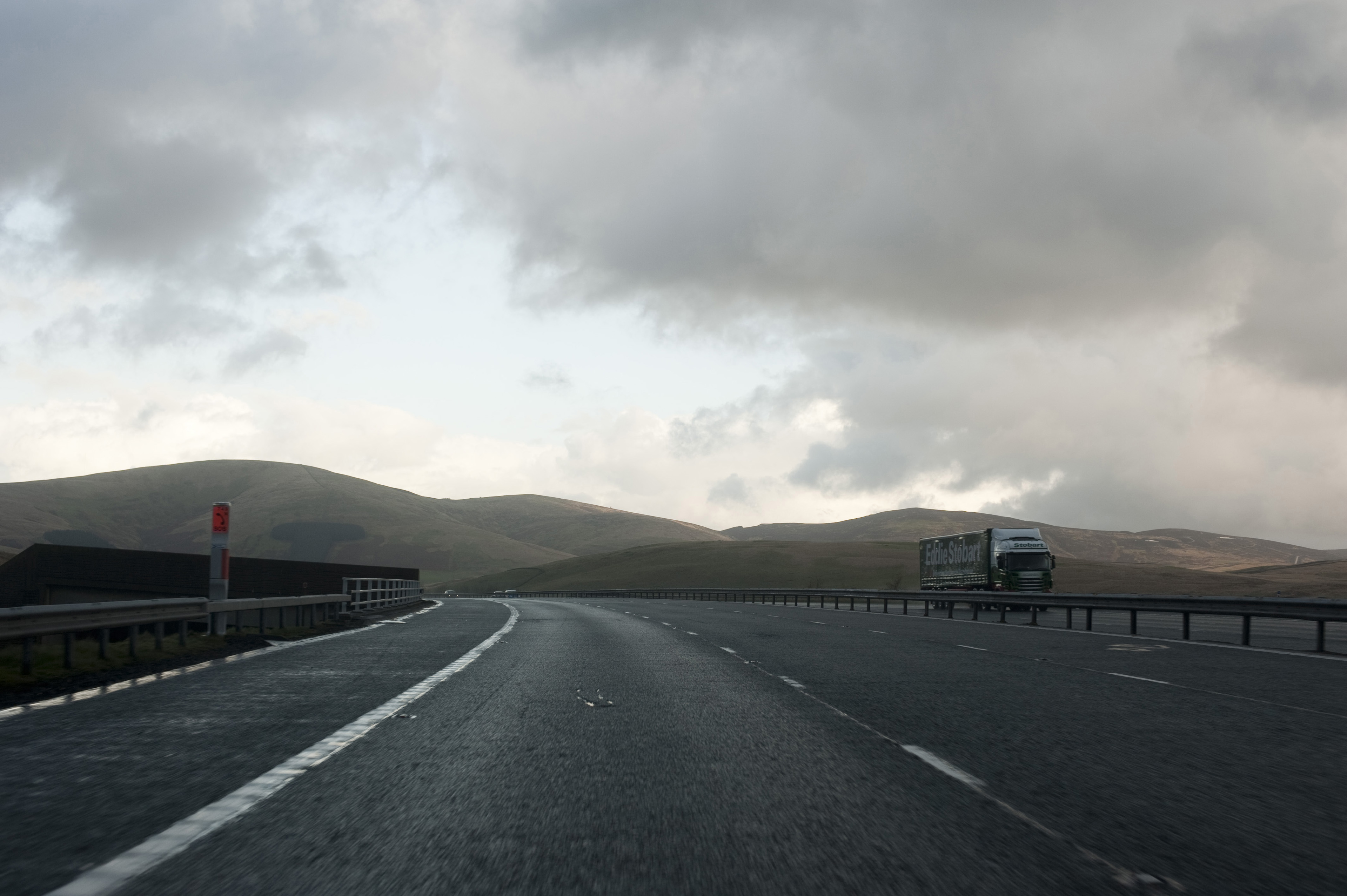 Traveling on a dual lane freeway with transport trucks and low lying stormy clouds, driver or passenger perspective
