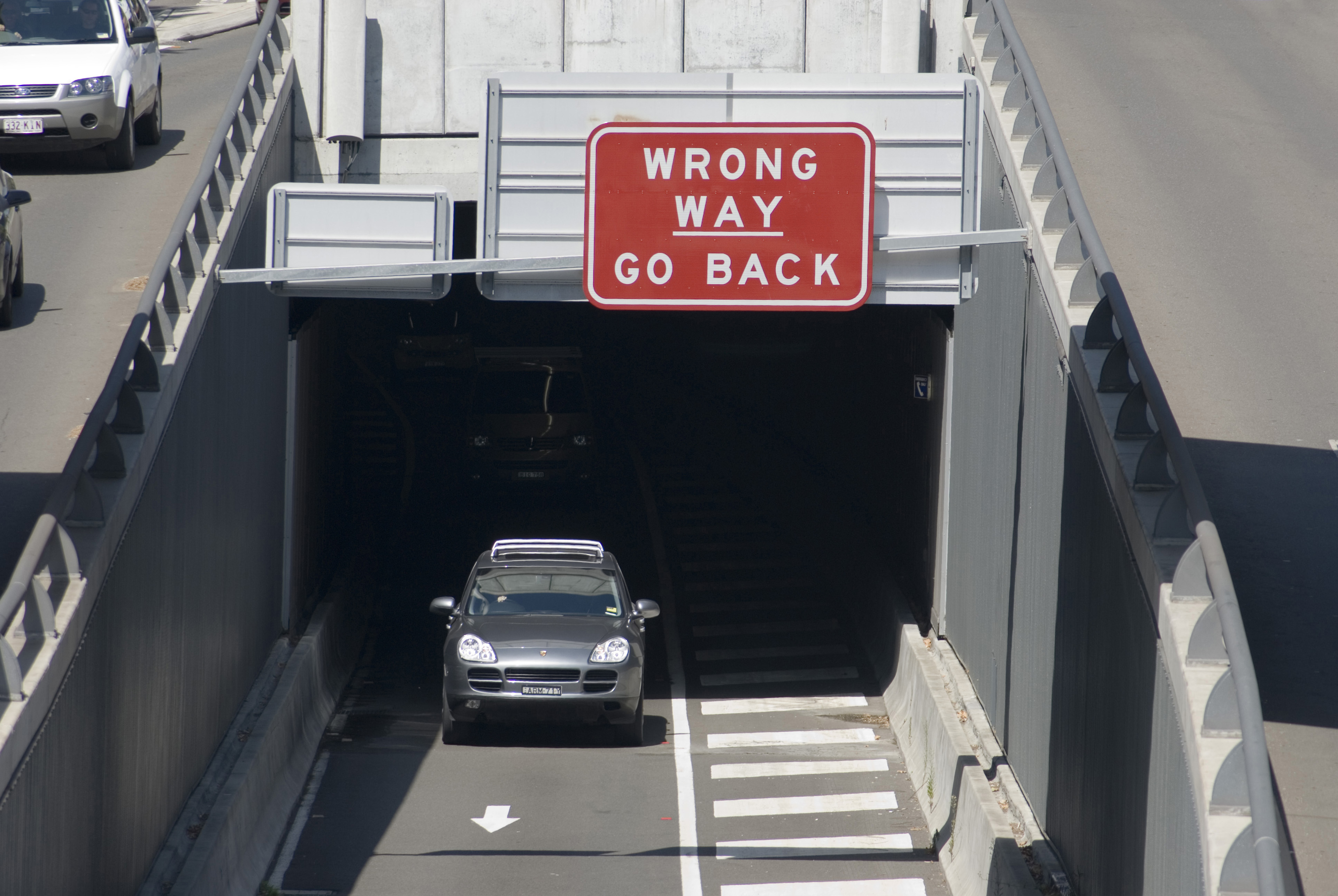 Car exiting a ramp onto the freeway under an overpass with the sign - Go Back Wrong Way