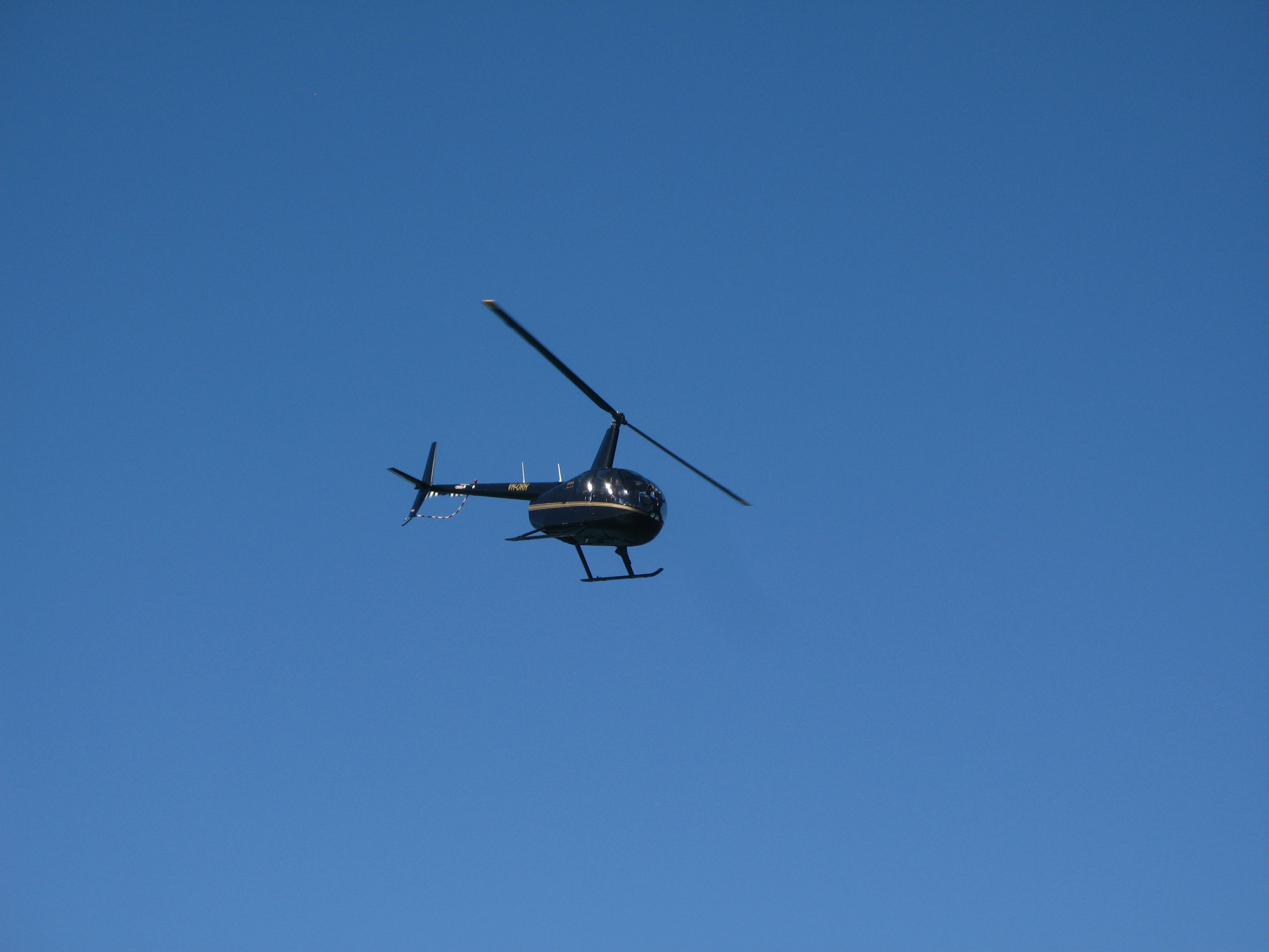 Black Helicopter Flying up in the Blue Gray Sky, Emphasizing Copy Space.