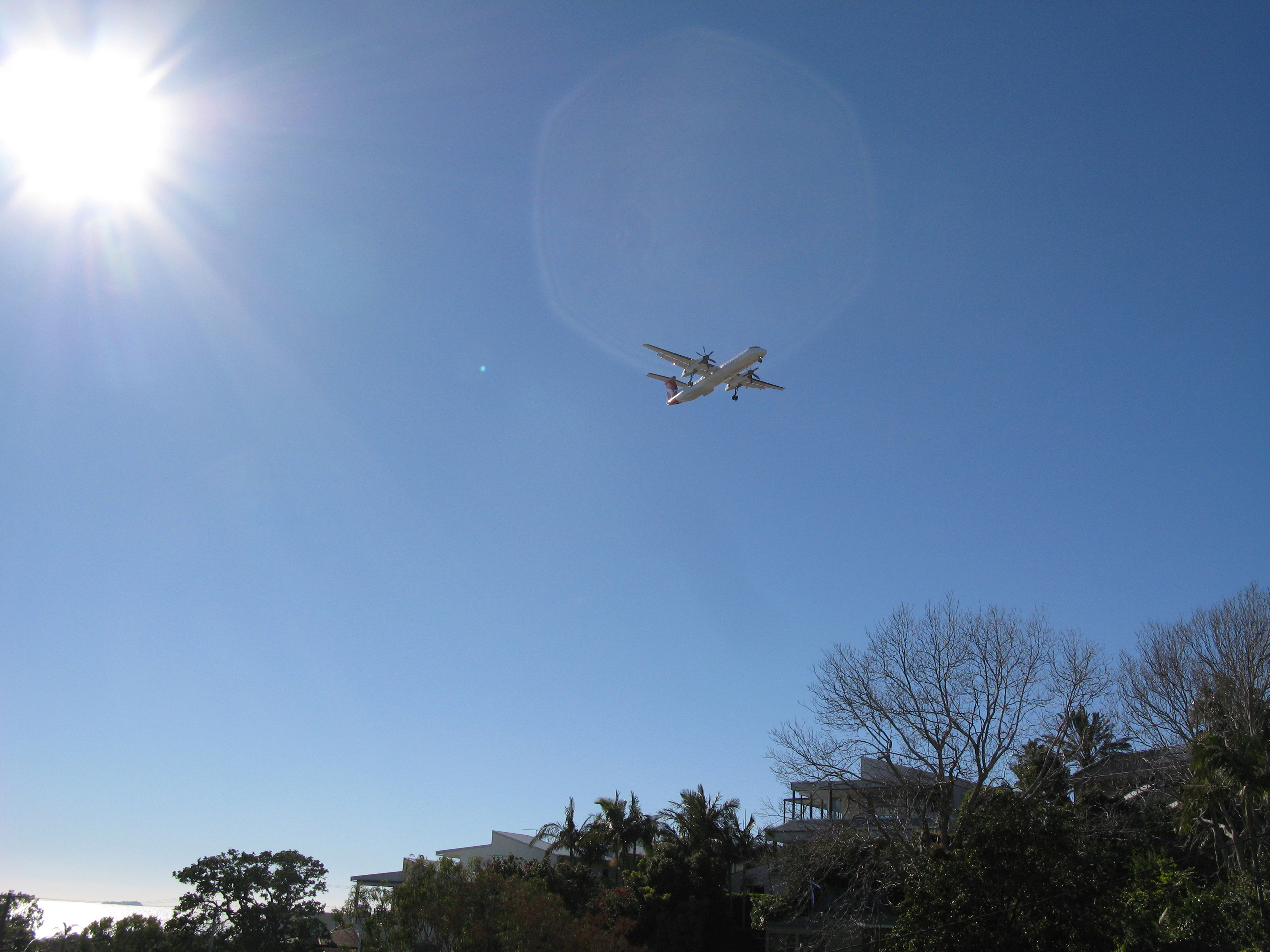 Low Angle View of Small Aircraft Flying over Hillside Homes in Large Blue Sky with Bright Sun