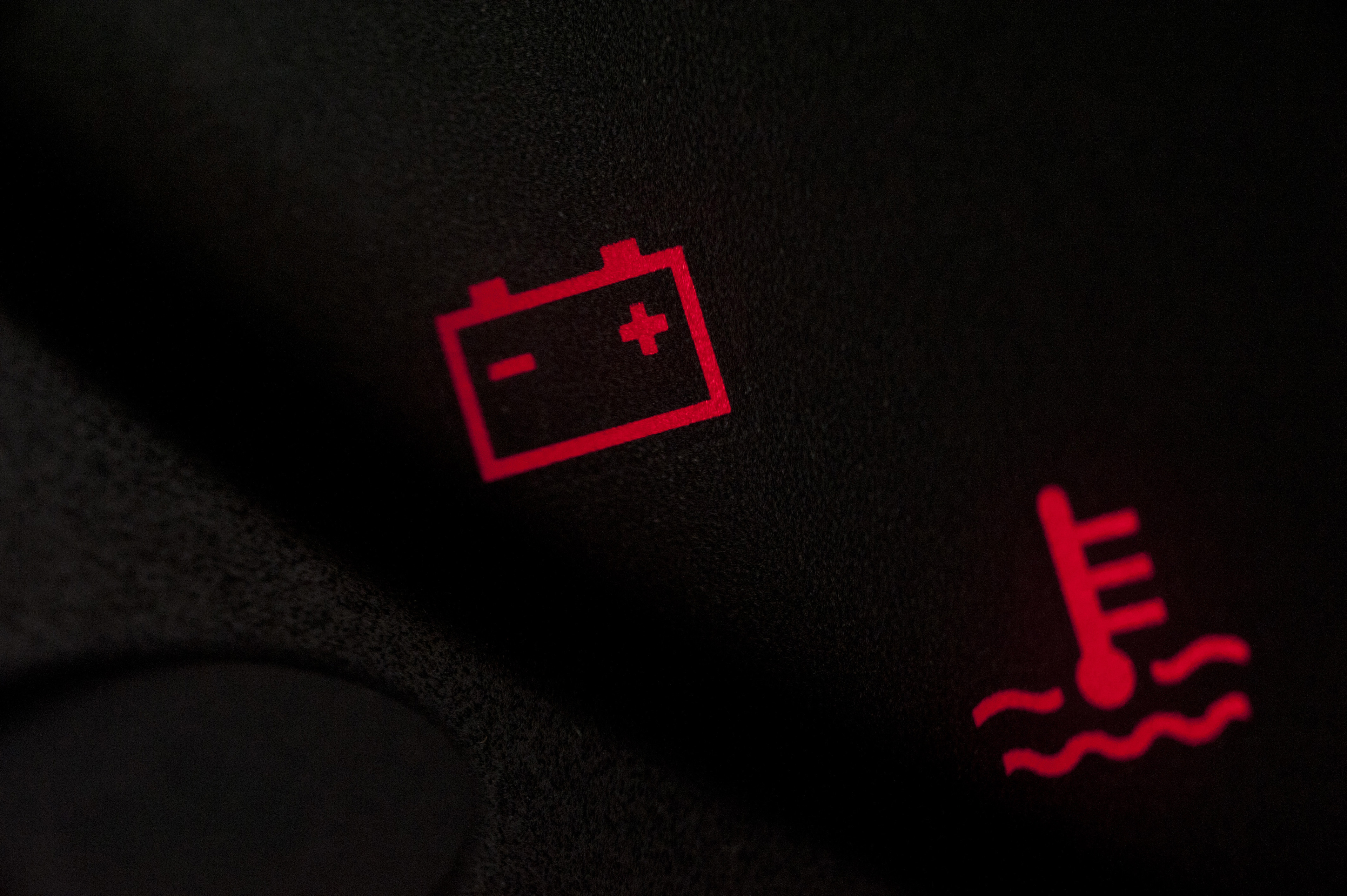 Battery and temperature or fuel warning lights illuminated in red on a vehicle display during ignition start up as the system checks for problems