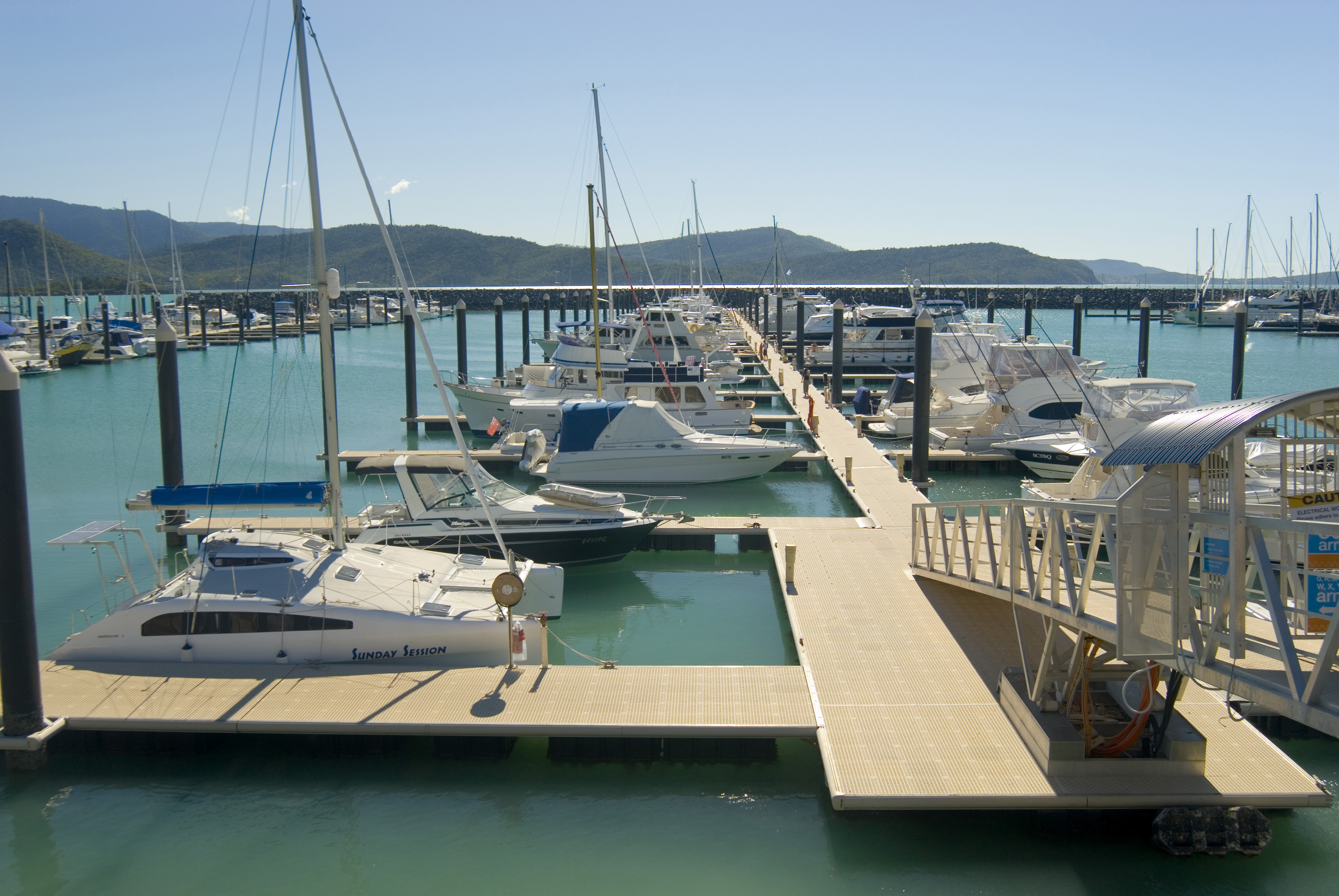 Yacht marina with moored boats alongside wooden floating pontoon jetties on a sunny summer day