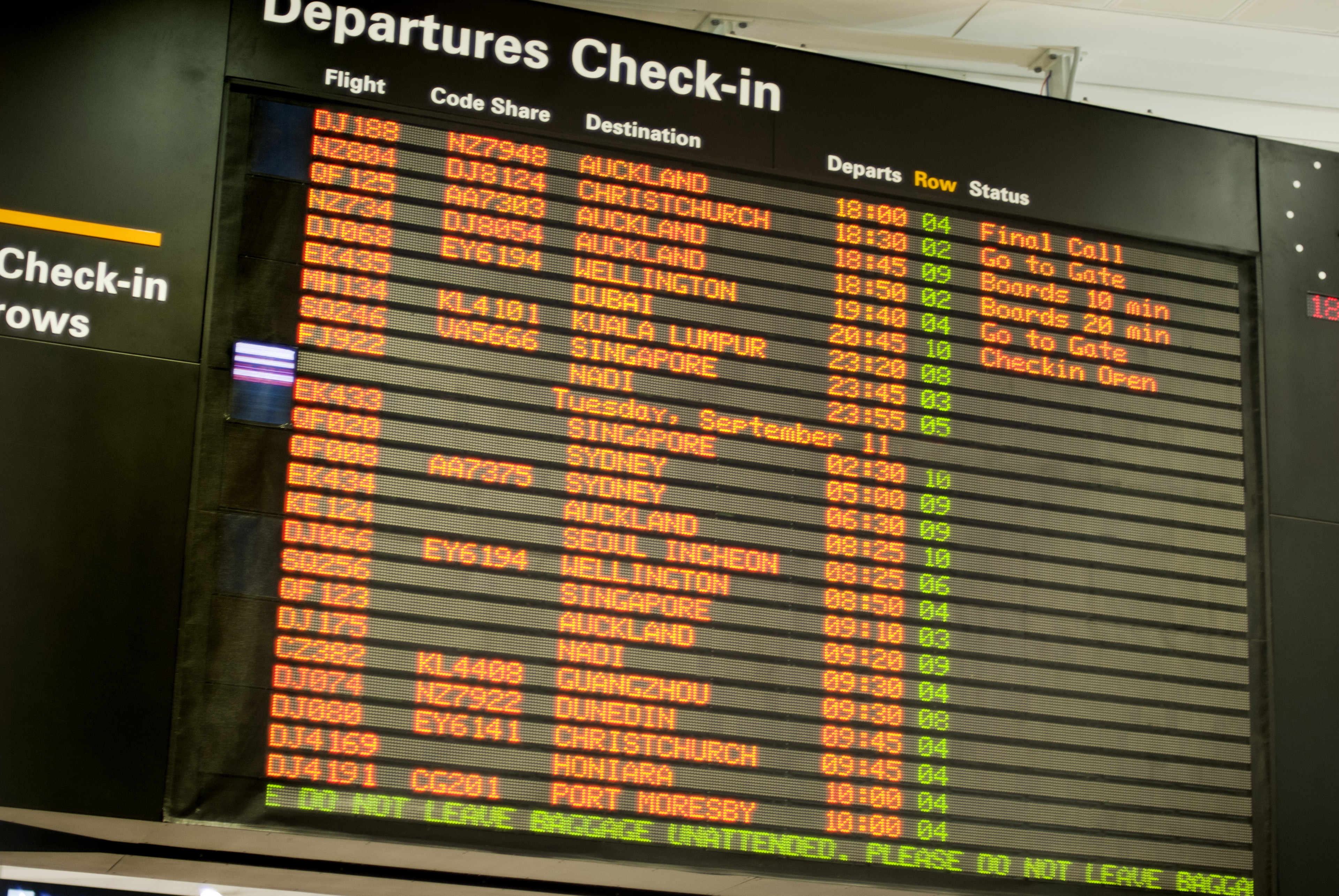 Flight information at the check-in for departures at an airport terminal with a board listing all flight information in a travel concept