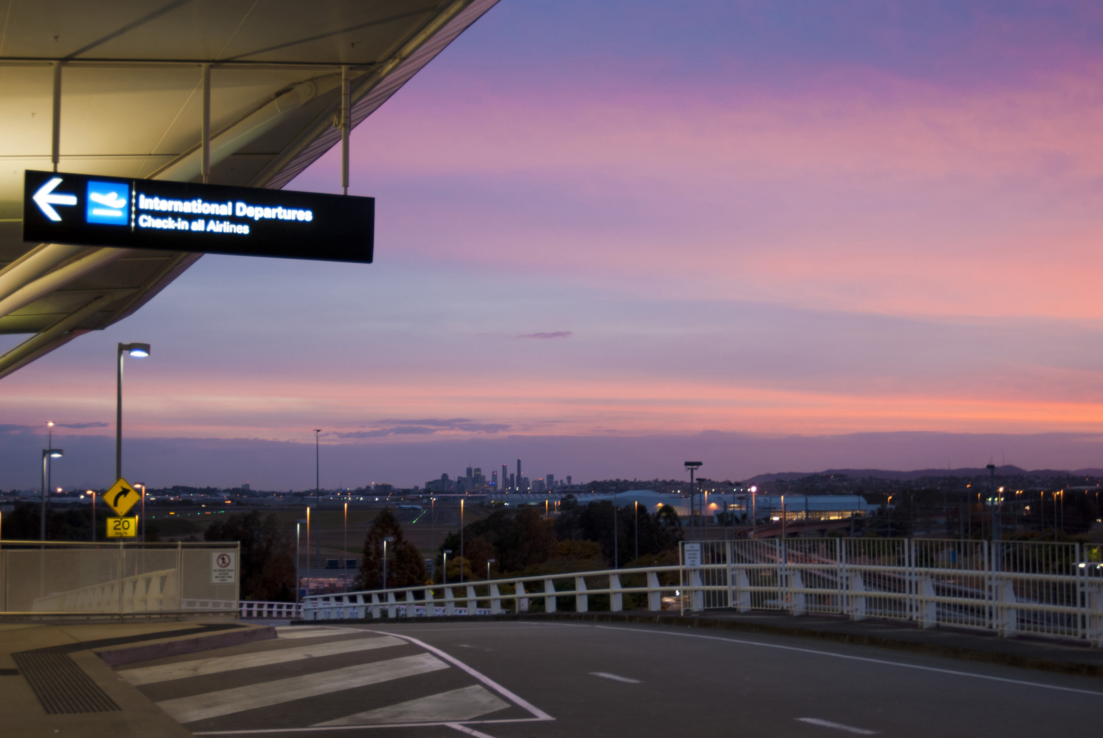 Drop off point outside an airport terminal with a view across the city at sunset with a colorful purple lilac sky