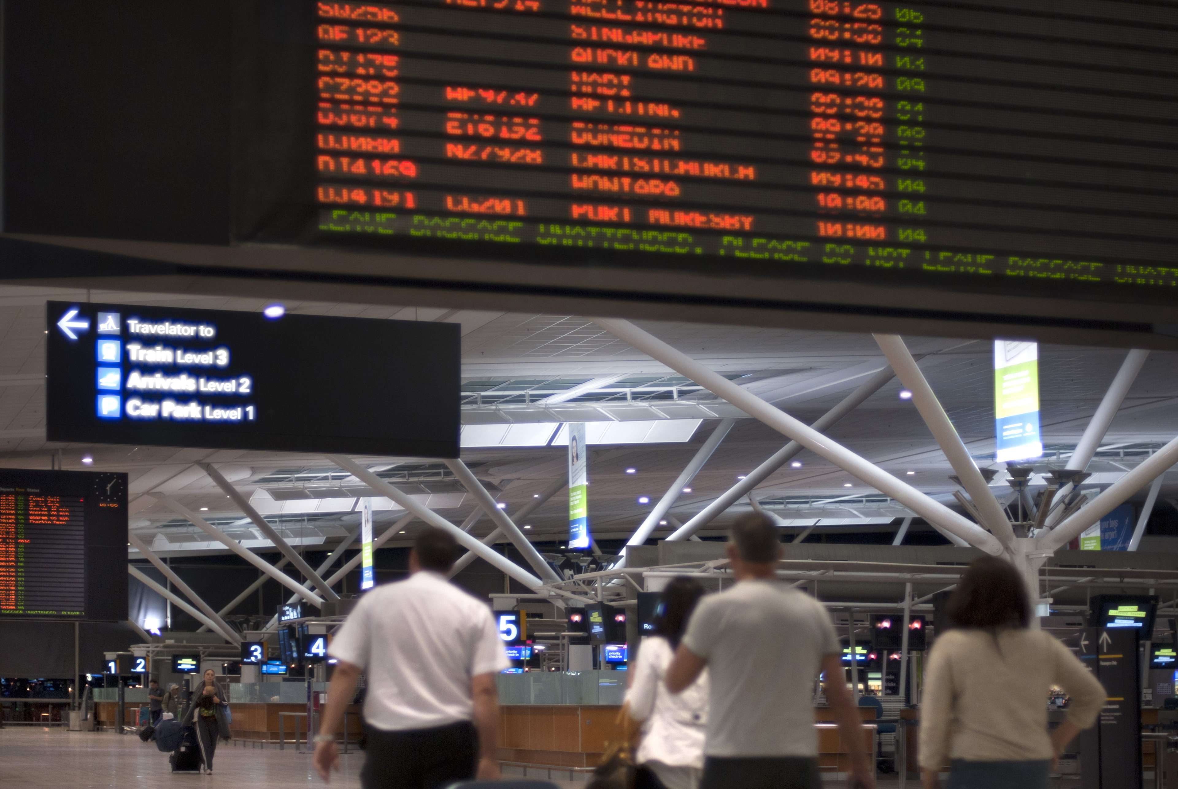 Passengers in an airport terminal building below the departures or arrivals board detailing the flights