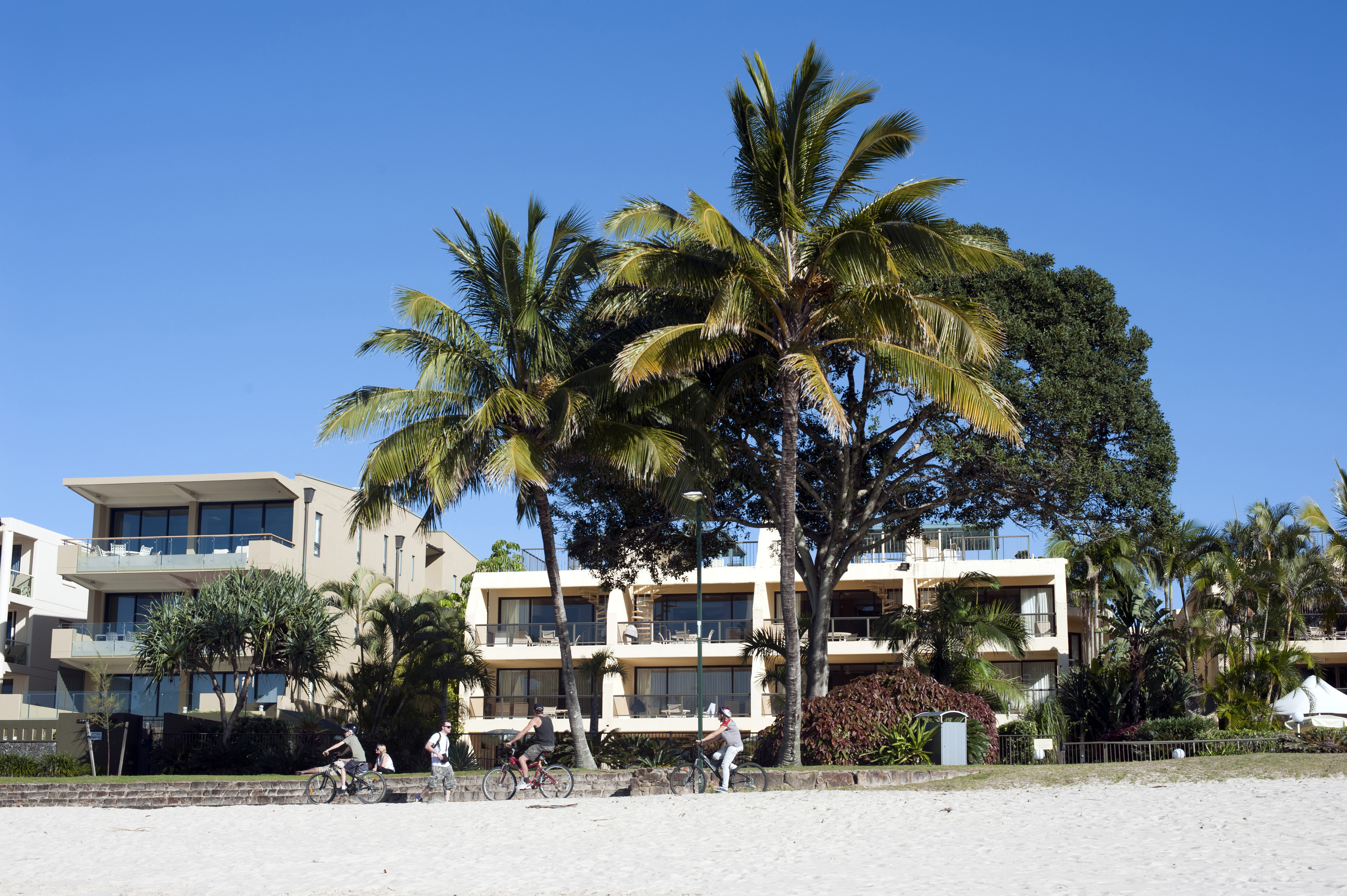 Group of People Riding Bicycles Past Low-Rise Beachfront Resort with Palm Trees