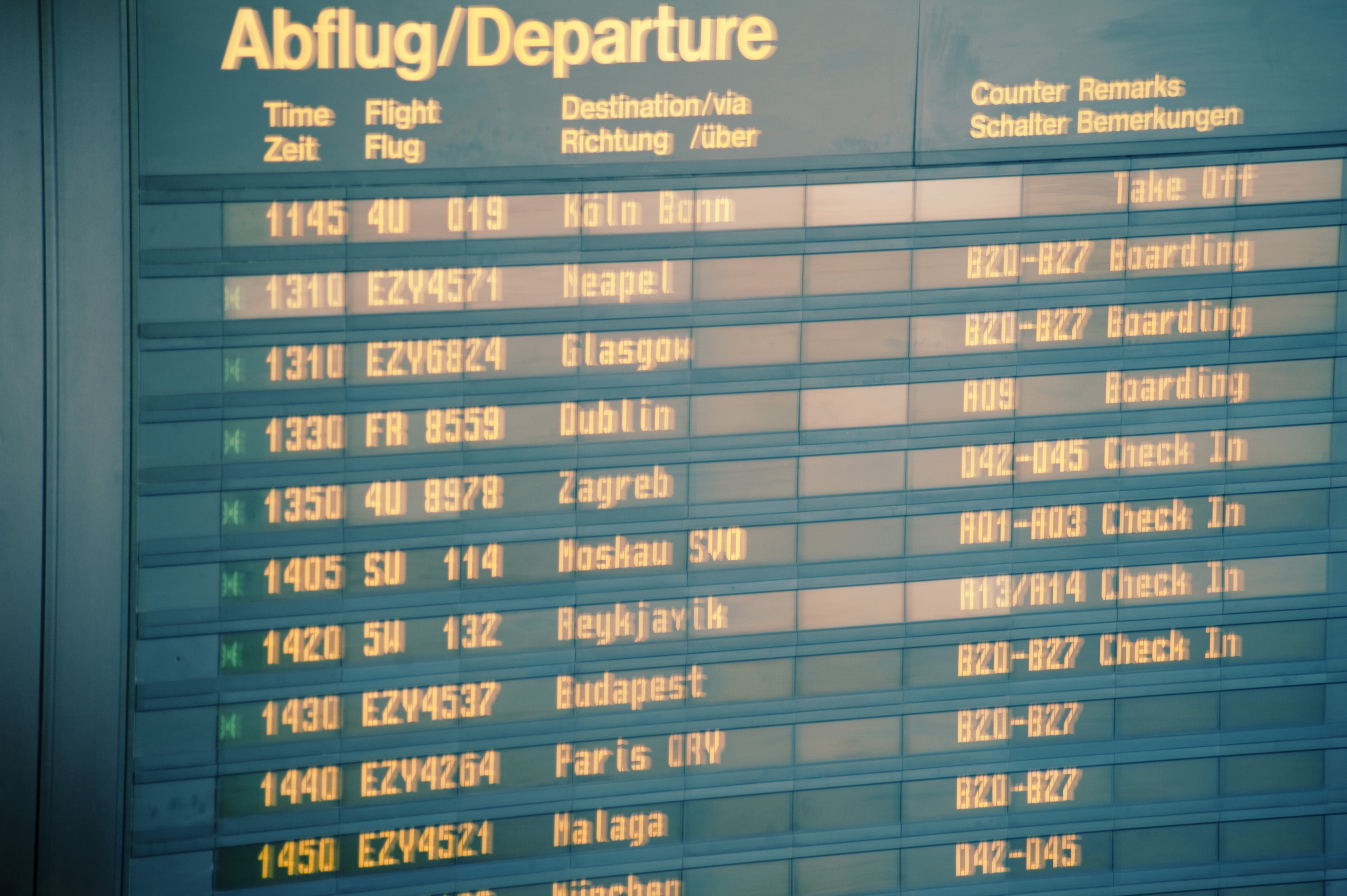 Departures sign board with flight details and times at an airport terminal, close up view conceptual of travel and tourism