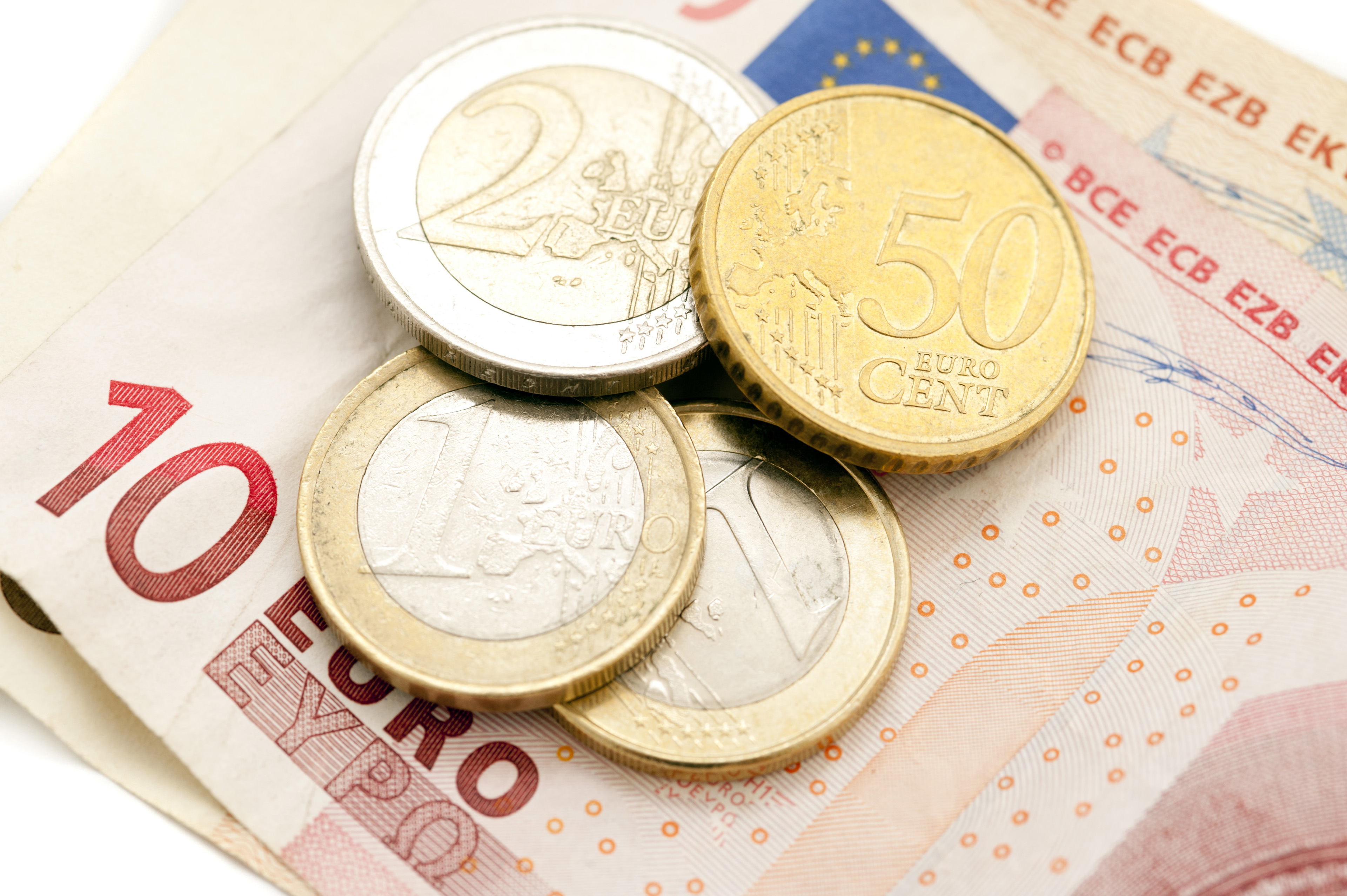 Financial background of a 10 Euro banknotes and assorted coins in a savings, payment, currency and earnings concept