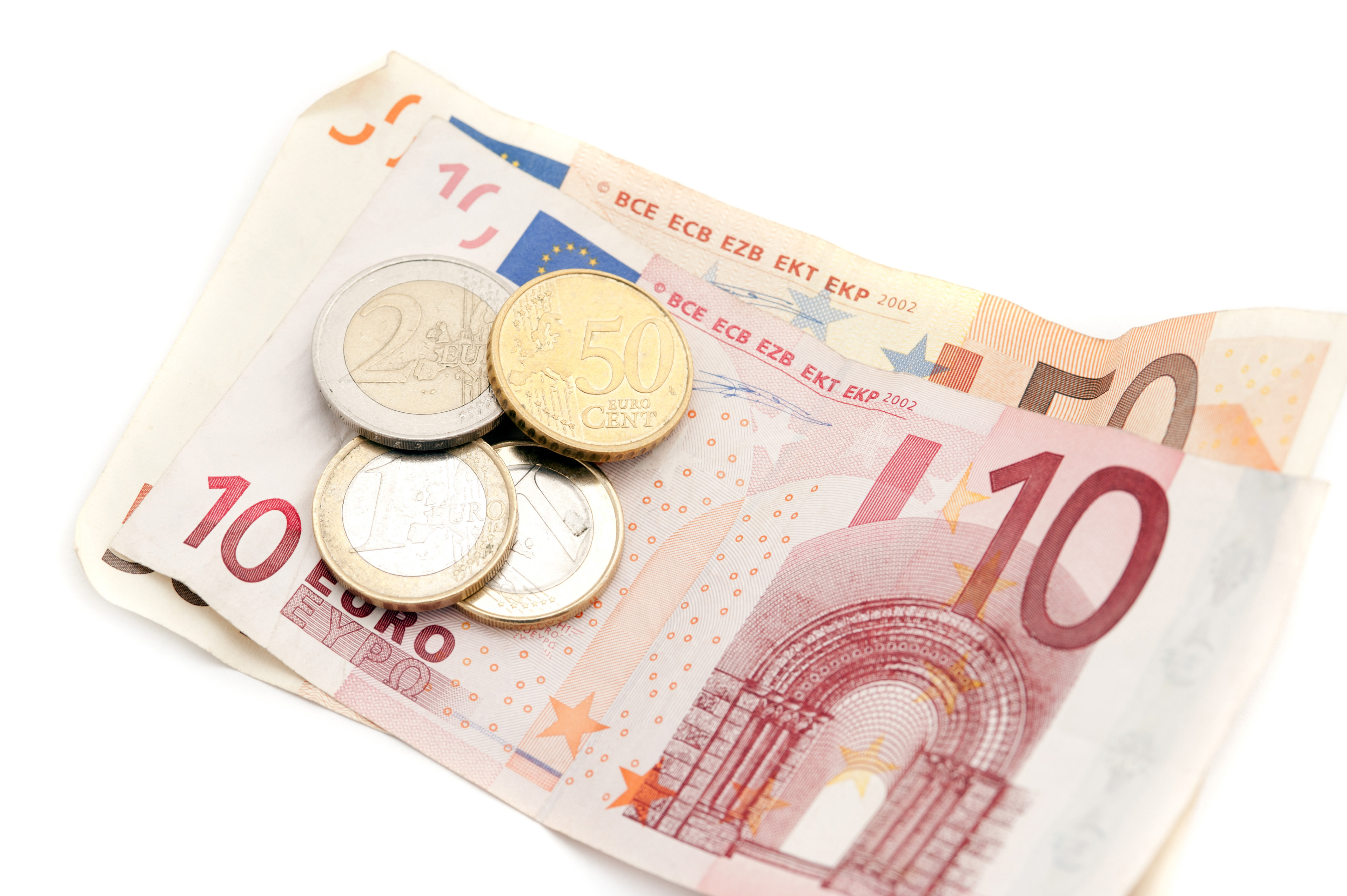 Euro 10 and 50 euro banknotes and coins lying on top of each other over a white background in a financial and currency concept