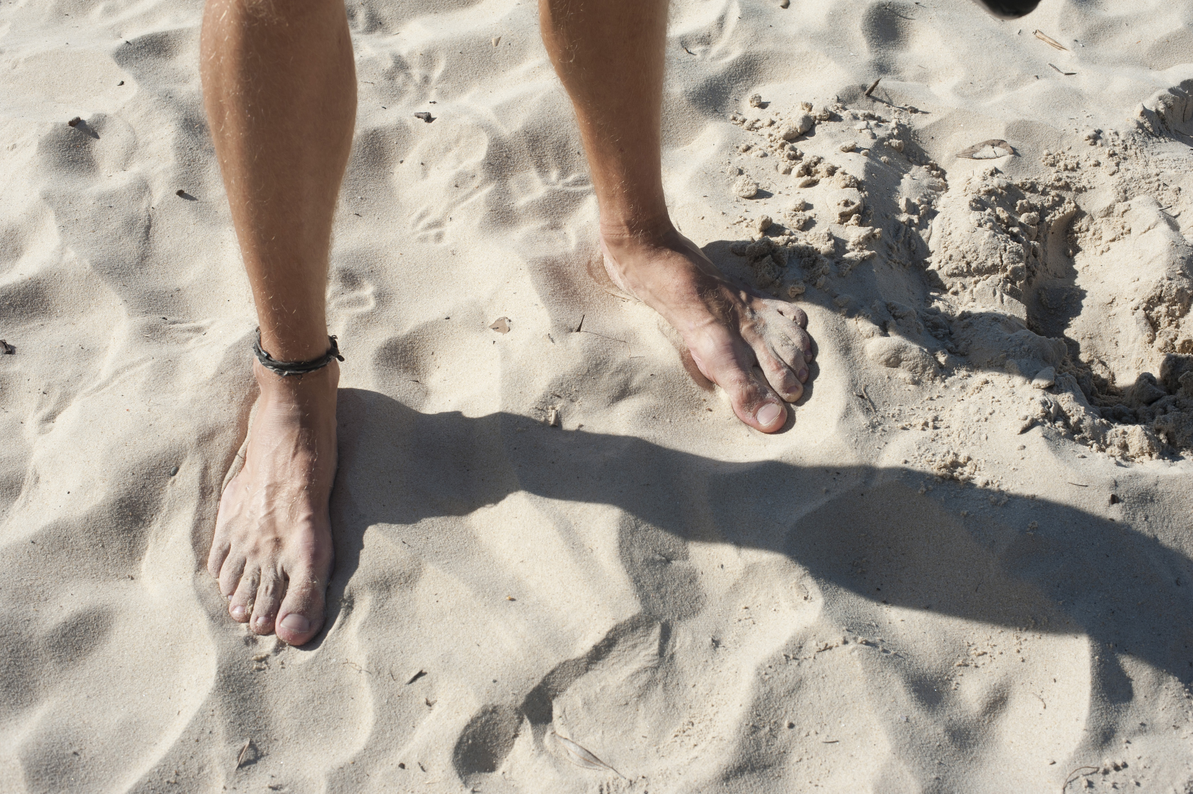 Close Up of Male Bare Feet with Ankle Bracelet Standing on Sandy Beach with Shadow from Bright Sun