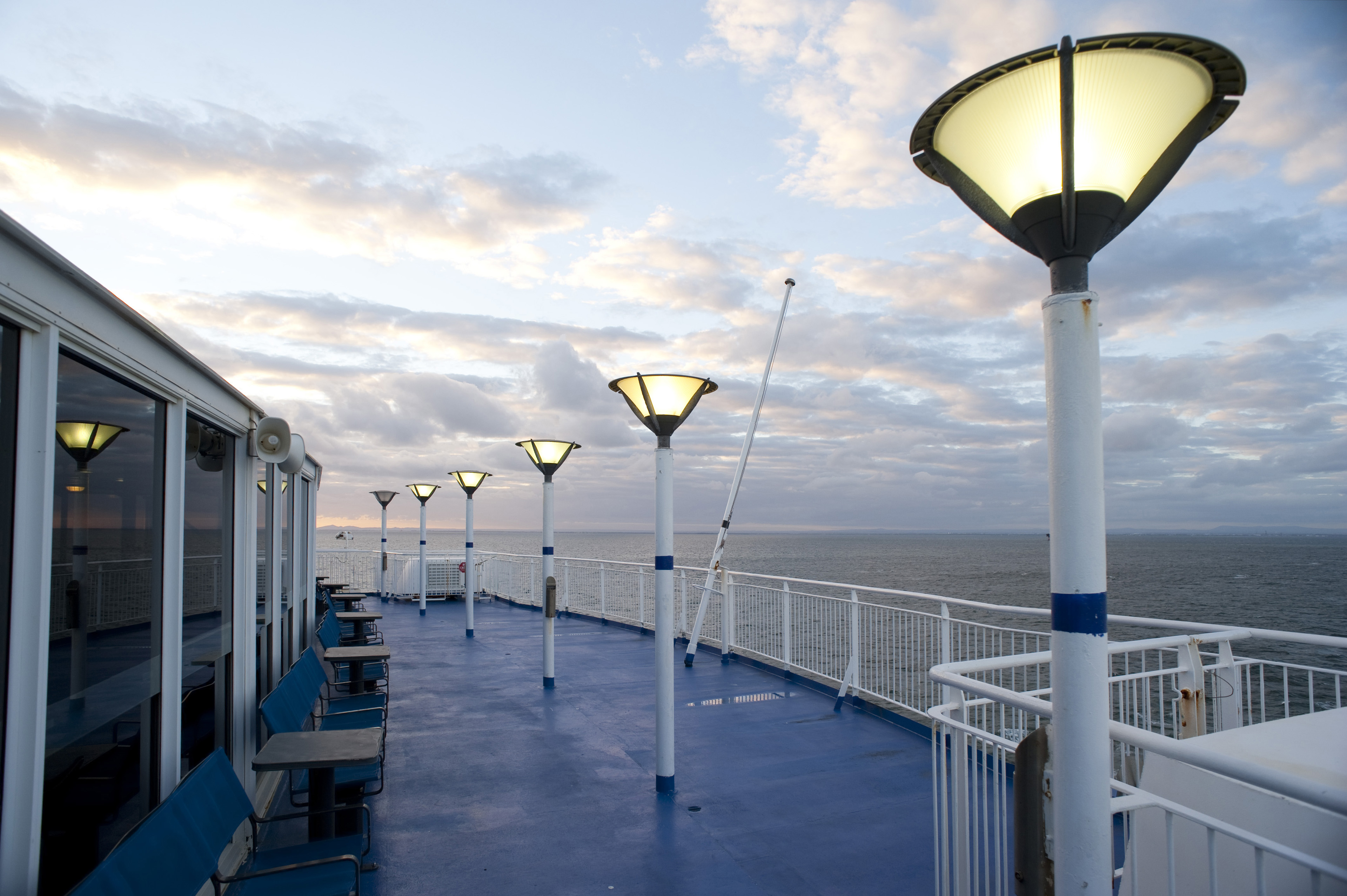 Deserted deck of a ferry in the evening with glowing lamps cruising mid ocean