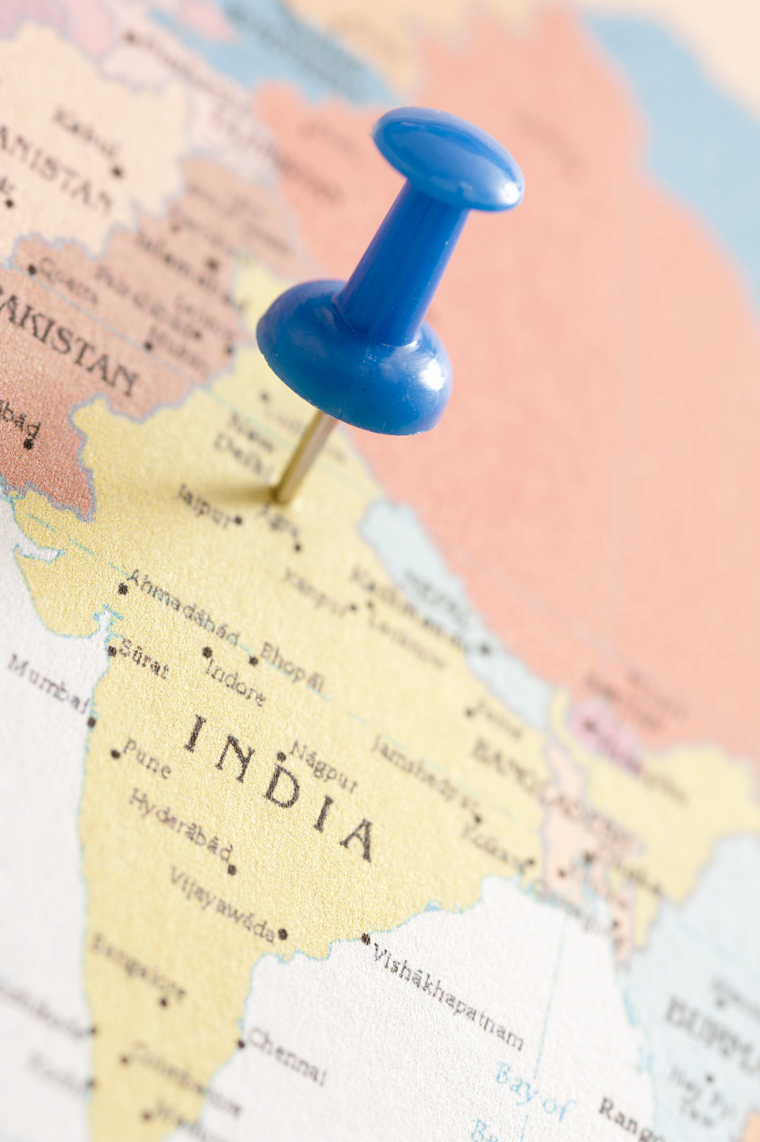 Close Up of Blue Thumb Tack Pinned into Map of India Marking Location of New Delhi