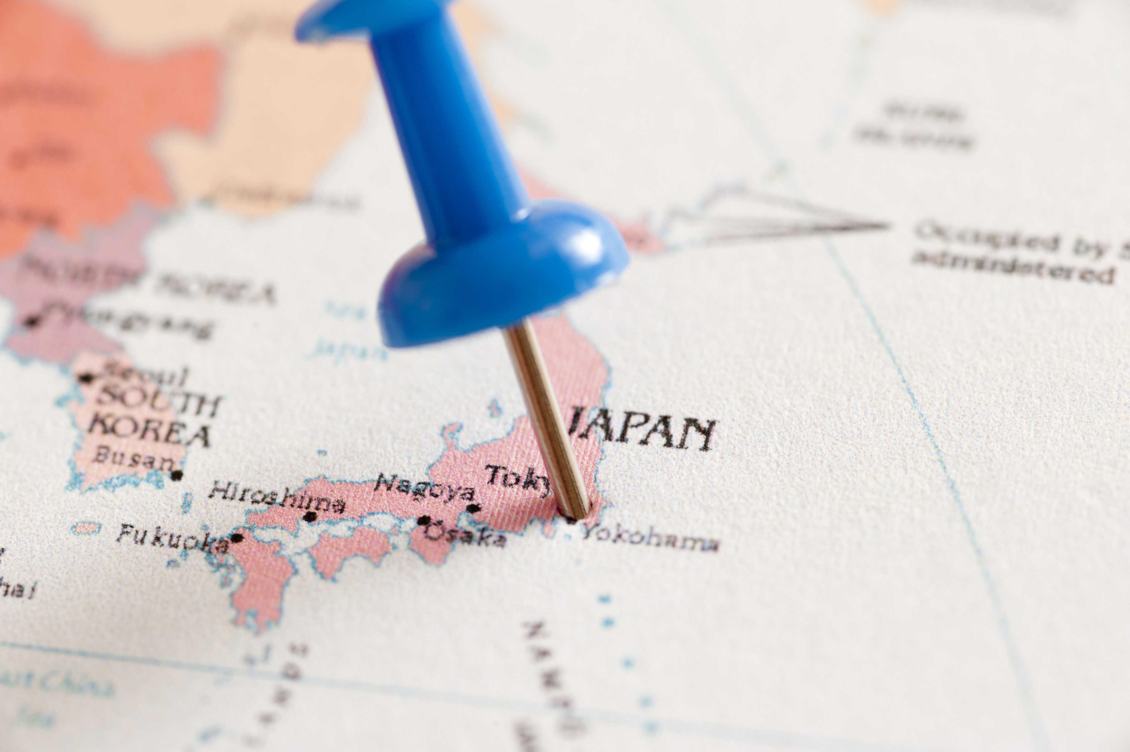 Close Up of Blue Pin Inserted into Map of Japan Pin Pointing Location of Tokyo
