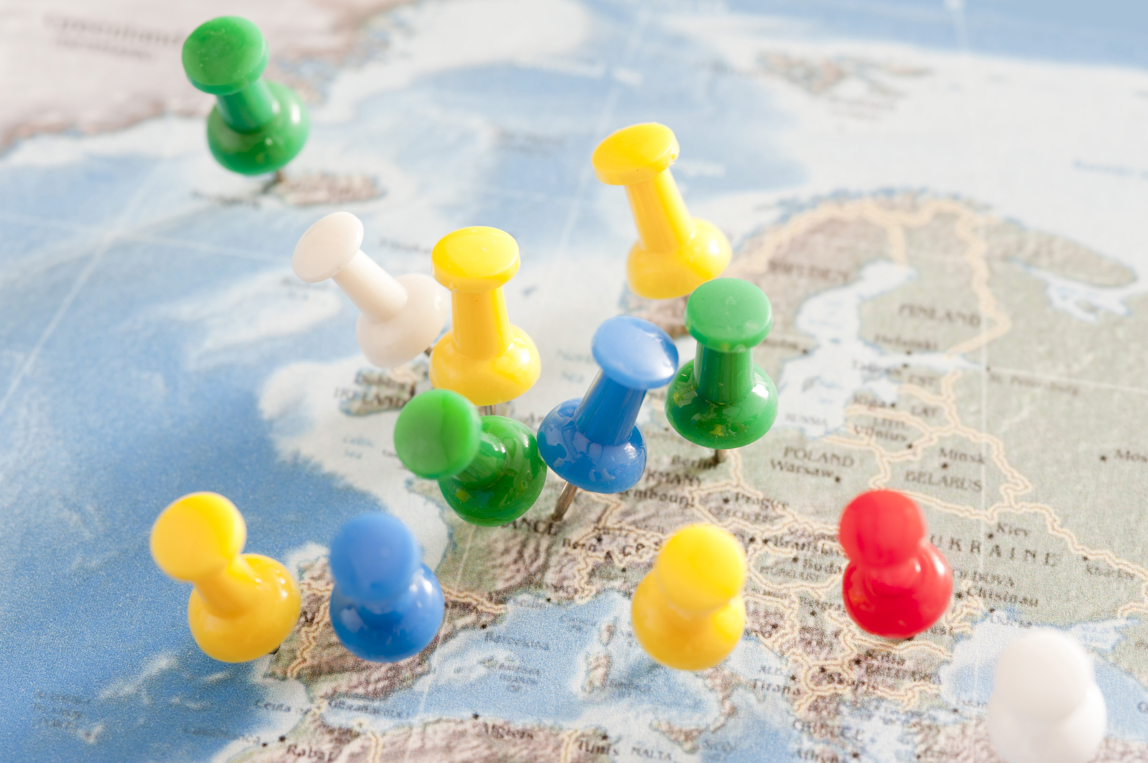 Close Up of Multiple Colorful Pins Inserted into Map of Europe in International Travel or Business Planning Concept