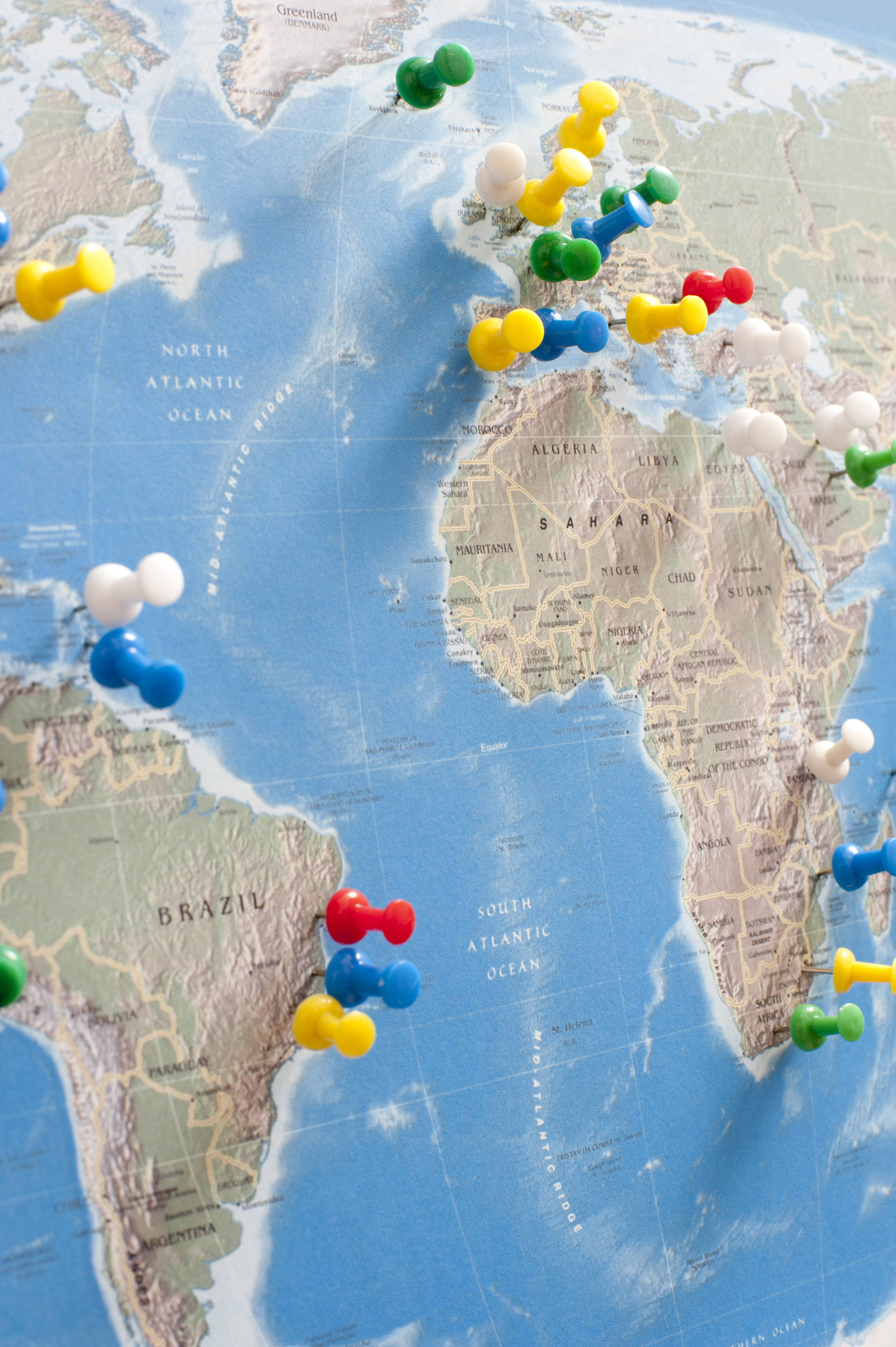 Various Multi-Colored Tacks Pinned into Multiple Locations Around the World on Wall Map