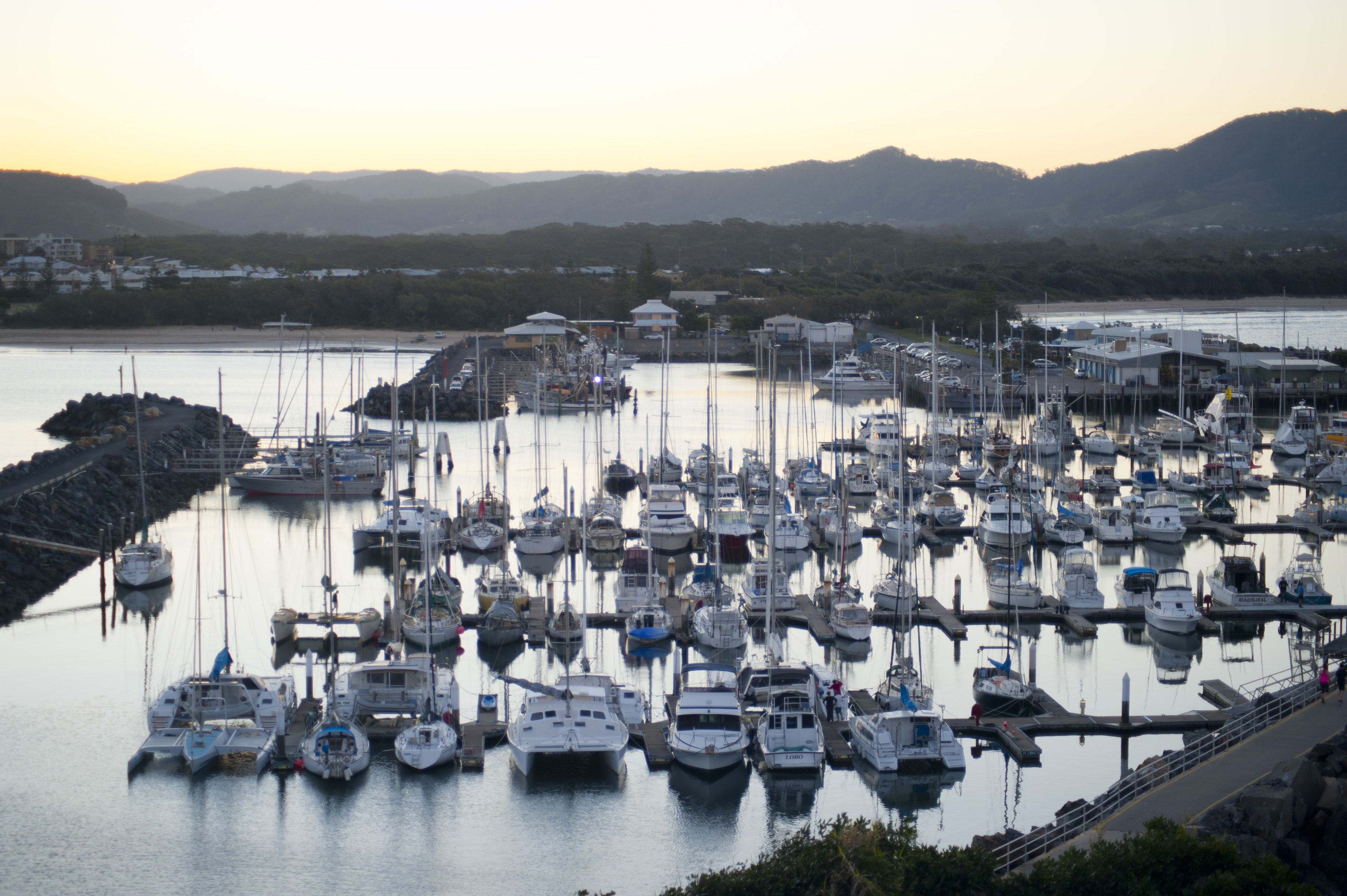 Evening view of rows of yachts moored in the calm sheltered water of a marina